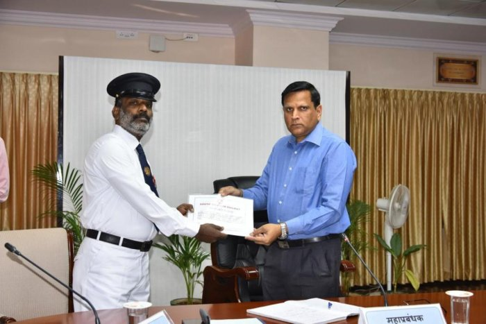 N Vishnoomurthy, senior passenger guard, receives a certificate from Ajay Kumar Singh, General Manager, South Western Railway, on Monday.