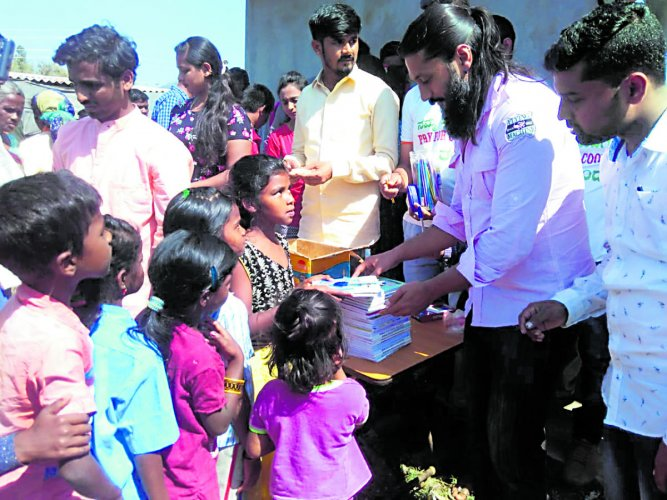 Actor Chetan distributes stationary items and sweets to the children at the Diddalli evacuees rehabilitation centre in Byadagotta near Kushalnagar.