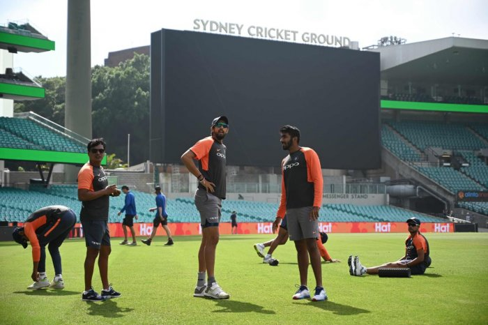 India's fast bowlers Ishant Sharma (centre L) and Jasprit Bumrah (centre R) warm up with their teammates before training ahead of the fourth and final Test against Australia at the Sydney Cricket Ground in Sydney on January 2, 2019. (Photo by Peter PARKS