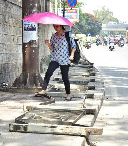 A pedestrian struggling to free walk while the barricade fell on footpath at Bannerghatta road in Bengaluru. DH Photo/Janardhan B K