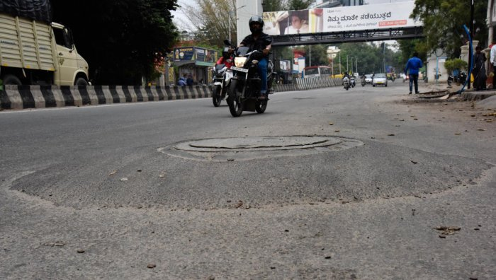 Manholes in many places are raised many inches above the road level. This one is on Kasturba Road in the heart of the city. The condition on roads in the interior neighbourhoods is worse. DH Photos by Janardhan B K and s k dinesh