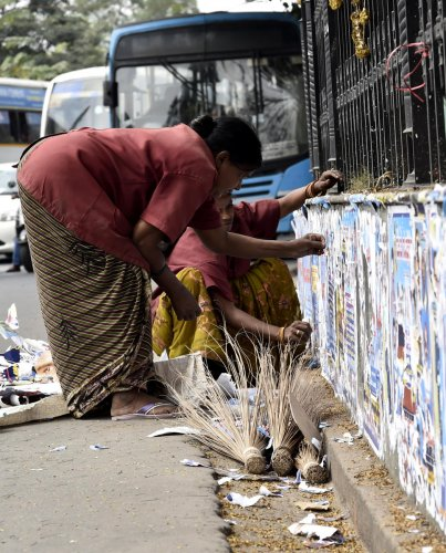 BBMP workers remove posters pasted on the walls of government buildings at KR Circle. DH file photo