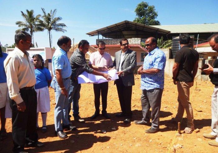 AKKA members inspect the land for the construction of the school building at Makkandooru in Madikeri taluk on Saturday.