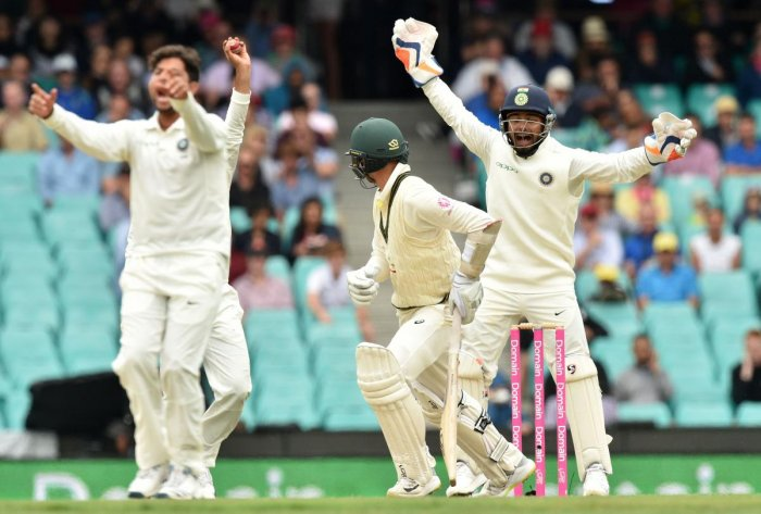 Australia's batsman Nathan Lyon is bowled LBW by India's Kuldeep Yadav (L), as India's wicketkeeper Rishabh Pant (R) shouts, on the fourth day of the fourth and final cricket Test at the Sydney Cricket Ground in Sydney on January 6, 2019. (AFP Photo)