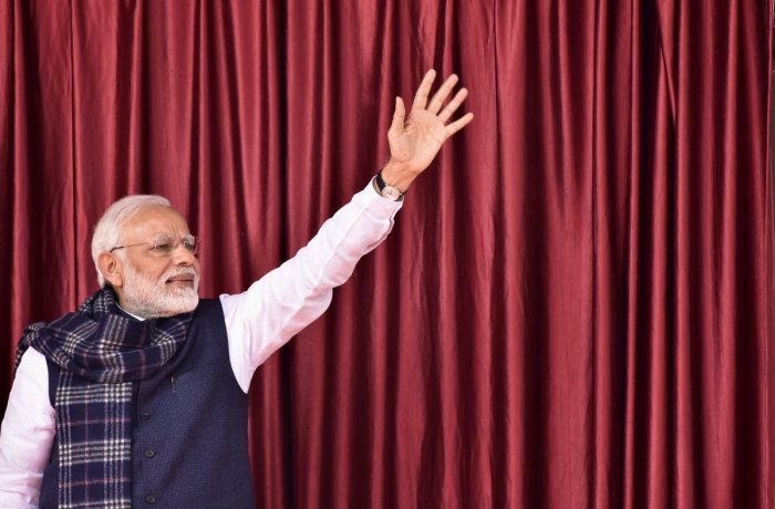 Prime Minister Narendra Modi waves to the crowd as he arrives in Medininagar on January 5 during a campaign sweep through Jharkhand state to inaugurate development projects. AFP