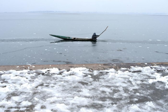 Kashmiri boatman breaks the ice to make his way on Dal Lake in Srinagar. PTI Photo