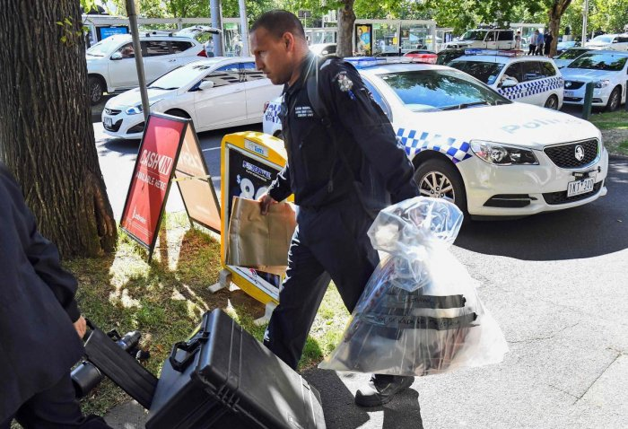 A Victoria Police forensic officer carries items to be loaded into a trailer outside the Italian consulate in Melbourne on January 9, 2019. - Australian police are investigating the delivery of suspicious packages sent to foreign embassies and consulates
