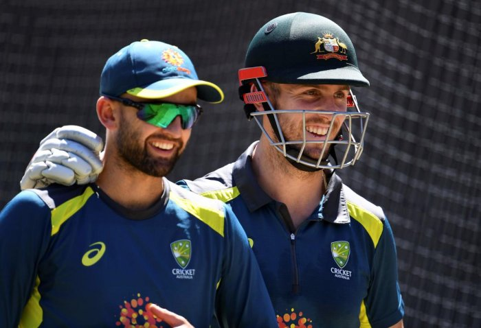 Australia's all-rounder Mitch Marsh (R) shares a lighter moment with teammate Nathan Lyon (L) during training in Melbourne. AFP file photo.