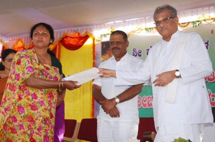 Dharmasthala Dharmadhikari D Veerendra Heggade hands over a cheque to a victim of natural calamity, as a part of the assistance programme under SKDRDP, in Madikeri on Thursday.