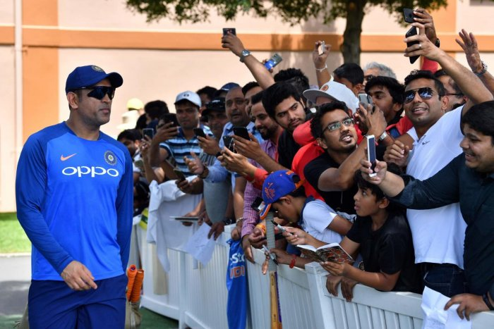 FOREVER, A STAR: Fans take selfies with India's Mahendra Singh Dhoni (left) prior to the team's training session in Sydney on Friday. AFP