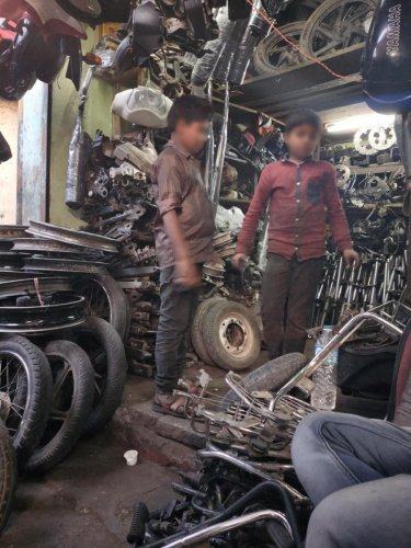 The street, near Russell Market, is lined with shops selling spares taken from old and discarded vehicles. (Right) Child workers are common.