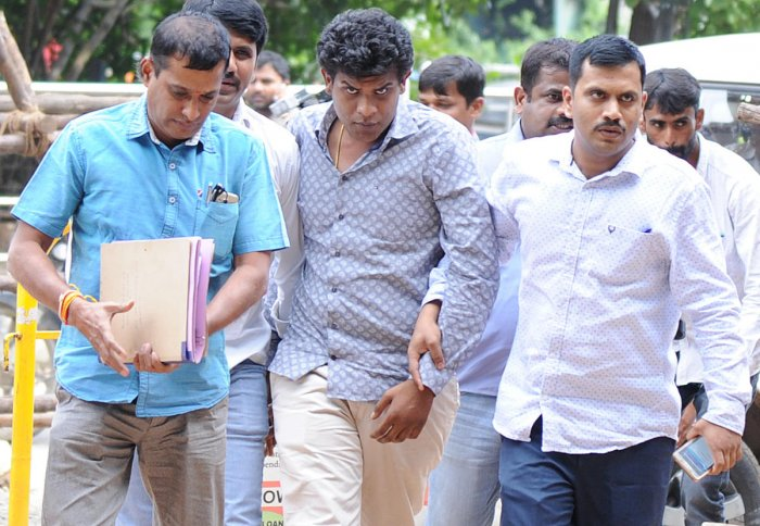 Geetha Vishnu (centre) being produced at a court in 2017. DH file photo