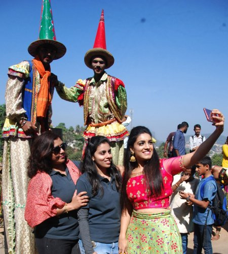 Tourists click a selfie with stilt artistes on Raja Seat Road in Madikeri.