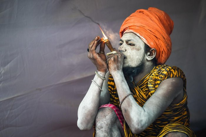 A sadhu smokes as he sits inside his tent among the Juna Akhara (a sadhu order) community at the Kumbh Mela festival. (AFP Photo)