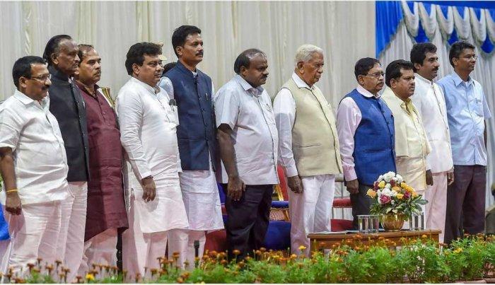 Governor Vajubhai Vala, Chief Minister H D Kumaraswamy and Deputy Chief Minister G Parameshwara with newly inducted ministers (from left), R B Thimmapur, 'MTB' Nagaraj, C S Shivalli, M B Patil, E Tukaram, P T Parameshwar Naik, Rahim Khan and Satish Jarkiholi at Raj Bhavan on Saturday. PTI Photo