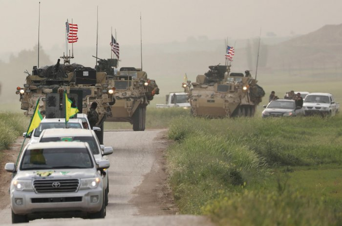 Kurdish fighters from the People's Protection Units (YPG) head a convoy of U.S military vehicles in the town of Darbasiya next to the Turkish border, Syria. Reuters file photo