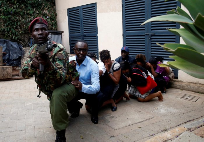 People are evacuated by a member of security forces at the scene where explosions and gunshots were heard at the Dusit hotel compound, in Nairobi, Kenya January 15, 2019. REUTERS