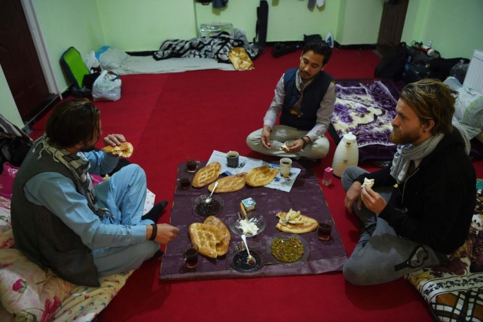 In this photo taken on November 11, 2018, Afghan Couchsurfing host Naser Majidi (C), 27, eats brekfast with his guests Norwegian tourist Jorn Bjorn Augestad (R), 29, and Dutch tourist Ciaran Barr, 24, at a house in Kabul. (AFP Photo)