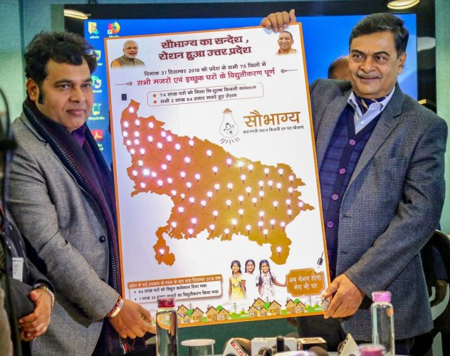 MoS (I/C) for Power and New and Renewable Energy Raj Kumar Singh with Power Minister of Uttar Pradesh Shrikant Sharma celebrate after reportedly achieving 100 percent household electrification under Saubhagya, in Uttar Pradesh. (PIB Photo via PTI)