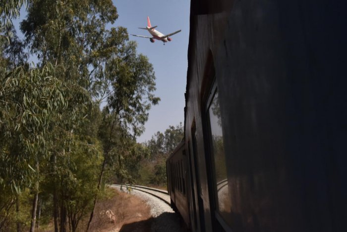 A flight about to land at the Kempegowda International Airport, as a DEMU train passes through an existing track close to the airport perimeter wall.