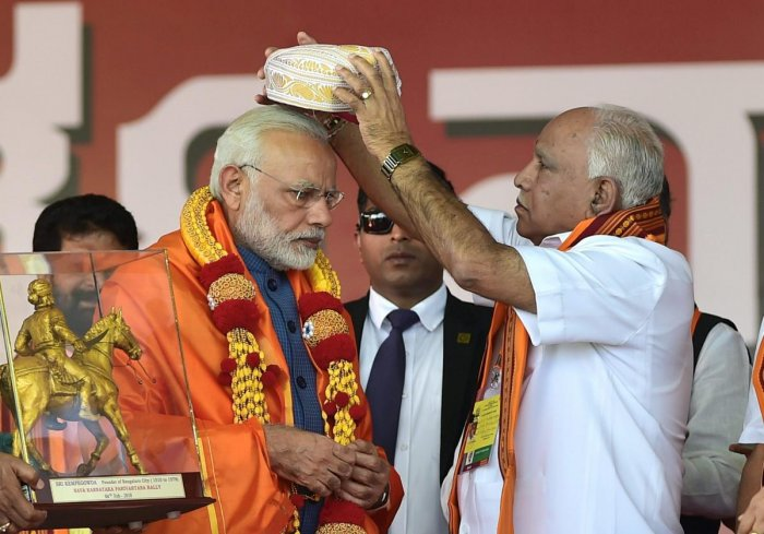 Prime Minister Narendra Modi being presented a Mysore Peta by State President B S Yeddyurappa during the Parivartan Yatra rally in Bengaluru. PTI
