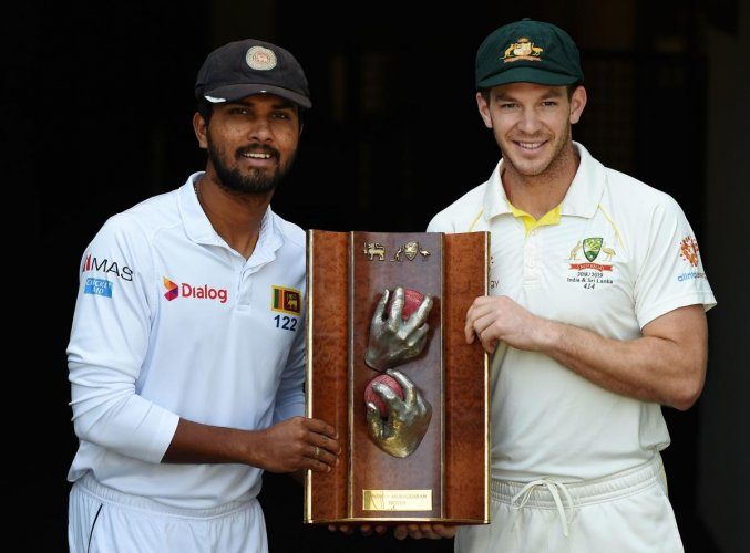 THE PRIZE: Sri Lanka's captain Dinesh Chandimal (left) and Australian counterpart Tim Paine pose with the Warne-Murali Test trophy at The Gabba on the eve of the opening match. AFP