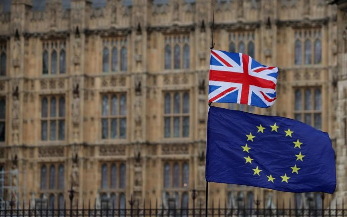 An anti-Brexit activist waves a Union and a European Union flag as they demonstrate outside the Houses of Parliament in central London. AFP