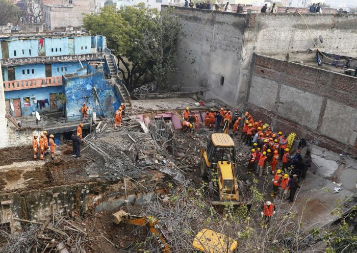 Rescue workers gather around the site of a newly constructed building that collapsed in Gurgaon, south of the Indian capital New Delhi. AFP Photo
