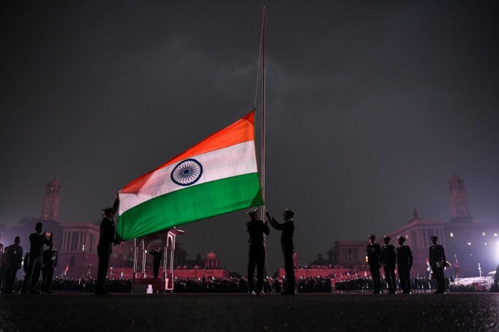 Indian Army personnel lower India's national flag during the rehearsal at the Beating Beating Retreat Ceremony at Vijay Chowk in New Delhi on January 24, 2019. - The ceremony is a culmination of Republic Day celebrations and dates back to the days when troops disengaged themselves from battle at sunset. (Photo by CHANDAN KHANNA / AFP)