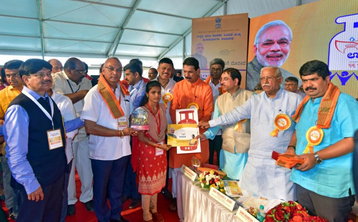 hairman of the Parliamentary Standing Committee on Petroleum and Natural Gas Pralhad Joshi and Union Minister Ramesh Jigajinagi hand over a sanction letter of LPG connection to a beneficiary at Prime Minister's Ujjwala Yojana beneficiaries' convention, held at B C Road in Bantwal on Friday.