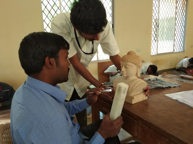 Hands on Tools: Sculptor chiseling an idol on sandalwood at the training centre.