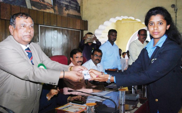 A first-time voter is given a voter identity card during the National Voters' Day programme in Madikeri.