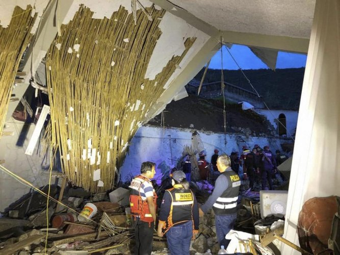 In this photo provided by Abancay police, officers and firefighters stand by a collapsed area of the Alhambra hotel in Abancay, Peru. Civil defence officials say the hotel wall collapsed during a wedding celebration, killing at least 15 people. (AP/PTI Ph