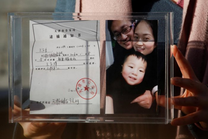 Li Wenzu, the wife of prominent Chinese rights lawyer Wang Quanzhang, holds a box with a family picture and the detention notice for her husband before shaving her head in protest in Beijing. Reuters.