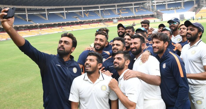 TIME TO SMILE: Saurashtra players pose for a selfie after beating Karnataka in the Ranji Trophy semifinal at the Chinnaswamy stadium in Bengaluru on Monday. DH PHOTO/SRIKANTA SHARMA R