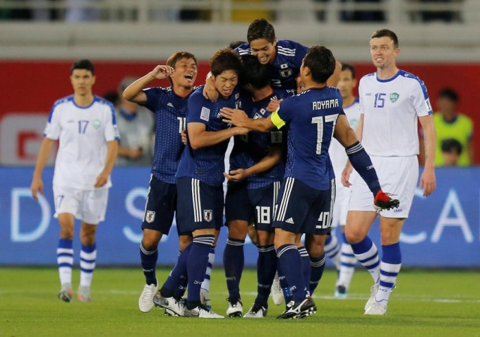 Japan players celebrate after scoring against Uzbekistan in their Group F game on Thursday. REUTERS