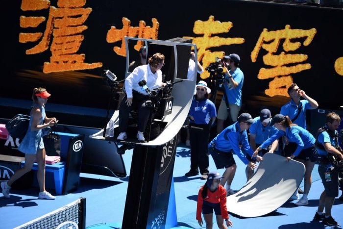 CLOSE SHAVE: Officials remove part of the umpire's canopy shade which was broken down by the spider-cam. AFP