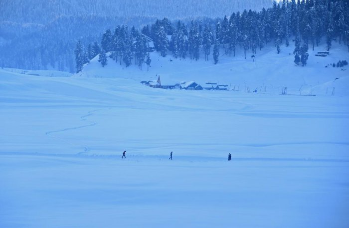 Tourists walk through a snow-covered area in Gulmarg, some 55 km north of Srinagar. AFP file photo.