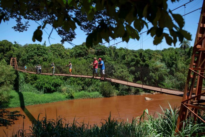 People stand on a bridge over the Paraopeba river, which was affected by mud, after the collapse of a dam at an iron-ore mine belonging to Brazil's giant mining company Vale near the town of Brumadinho, state of Minas Gerais, southeastern Brazil, on Janua