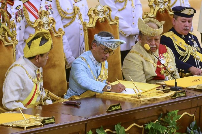 Sultan Abdullah Sultan Ahmad Shah, (2nd-L) signs a document after taking the oath at the National Palace in Kuala Lumpur. AFP