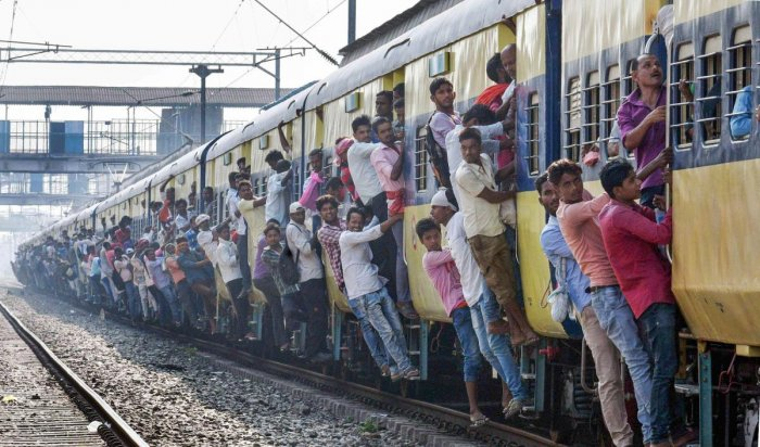 Commuters lean out of an overcrowded local train on the day of Railway Recruitment Board Examination (RRB), in Patna, in 2018. PTI