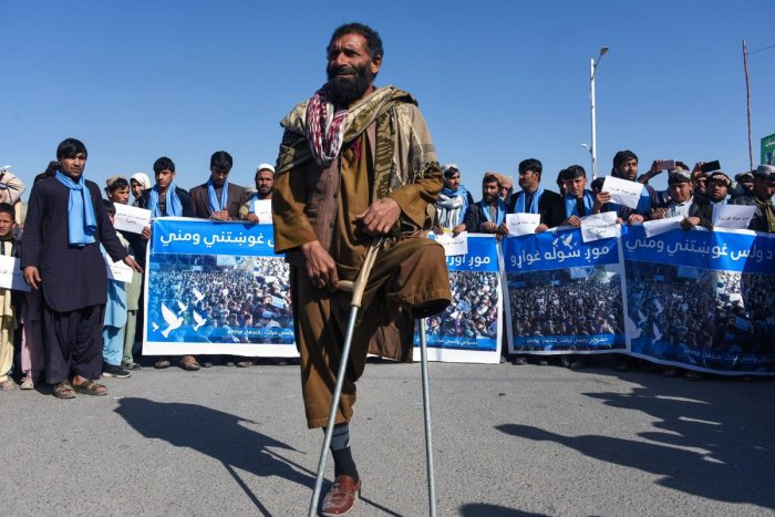 Afghan protesters march for peace and ceasefire as they hold banners in the Kandahar province on January 17, 2019. AFP