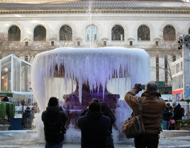 People photograph a mostly frozen Bryant Park fountain, as record low temperatures spread across the Midwest and Eastern states, in New York City (REUTERS)