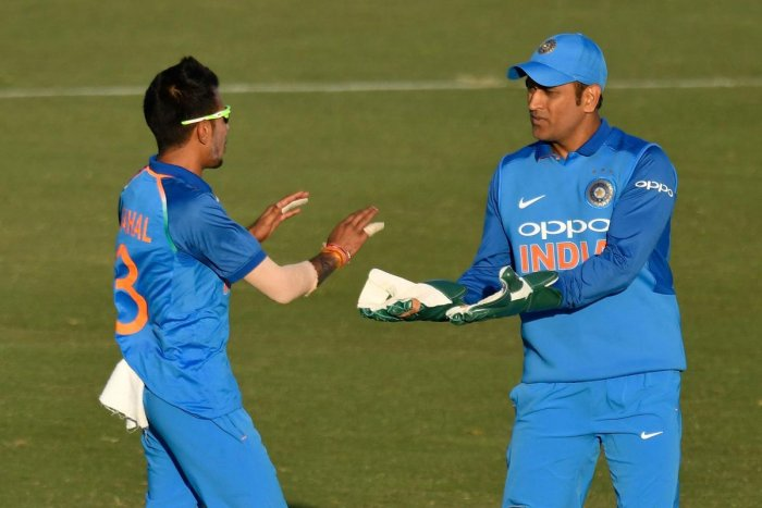 Yuzvendra Chahal (L) celebrates taking the catch of New Zealand's Martin Guptill with teammate keeper MS Dhoni during the second one-day international match between New Zealand and India. AFP file photo.