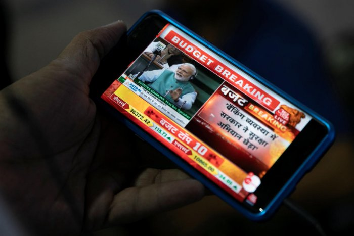 Prime Minister Narendra Modi is seen as a commuter watches telecast of the interim budget speech on his mobile phone at a railway station in Mumbai, February 1, 2019. REUTERS