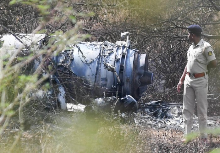 A police officer inspects the wreckage of the Mirage-2000 fighter aircraft after it crash landed at HAL airport, soon after taking-off for a training sortie in Bengaluru on Friday. (DH Photo/ B H Shivakumar)