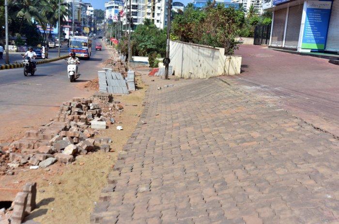 Construction materials being carelessly dumped along Bejai Main Road in Mangaluru.