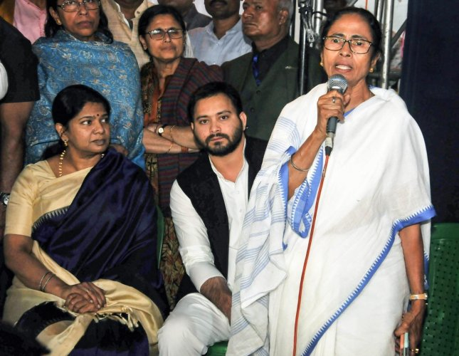 West Bengal Chief Minister Mamata Banerjee addresses the public at the dharna site in Kolkata on Monday. DMK MP Kanimozhi (left) and RJD leader Tejashwi Yadav (centre) look on. PTI