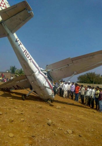 People look at the wreckage of a crashed aircraft, which was being used for civil aviation training, in Pune district, Tuesday, Feb. 5, 2019. (PTI Photo)