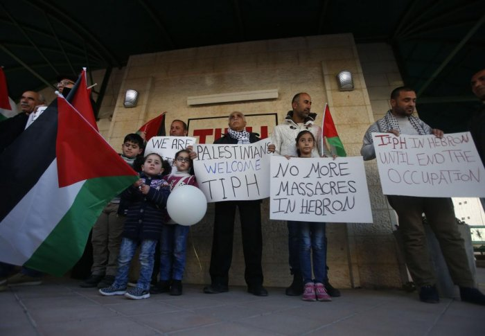 Palestinians carry national flags as well as placards denouncing the Israeli prime minister's recent decision not to renew the mendate of The Temporary International Presence in Hebron (TIPH), in the occupied West Bank city on January 30, 2019. (AFP)